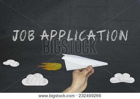 Job Application Concept On Blackboard. Hand Holding Paper Plane