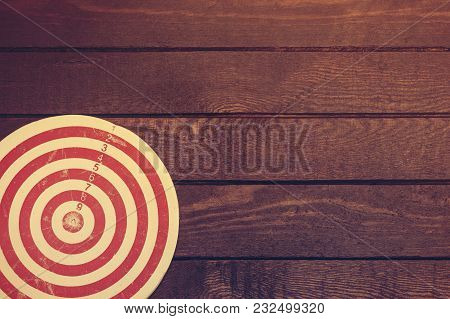 Dart Board On Dark Wooden Table. Business Concept. Copy Space For Text. Toned