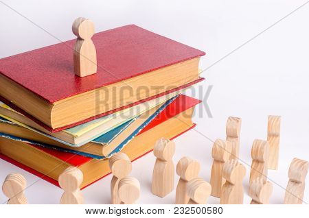 A Man Stands On A Pile Of Books Before The Audience And Makes A Speech. A Smart Leader Manages Emplo