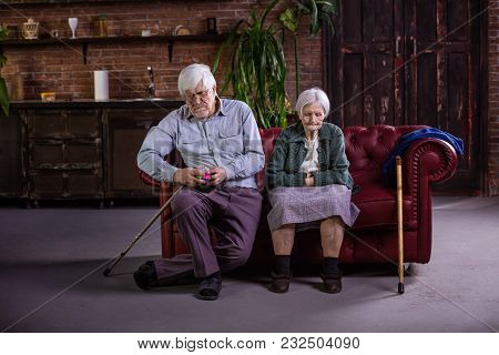 Senior Couple Sitting On Couch. Couple In Quarrel, Not Talking To Each Other. Man Playing With Puzzl