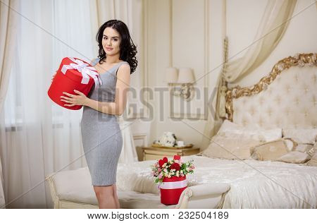 Beautiful Young Woman Holding Gift Box At Home And Smiling