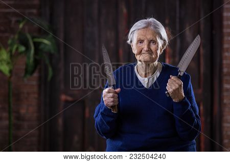 Senior Woman Holding Kitchen Knives Indoors. Security And Self-defense Concept. Could Be Used In Hum