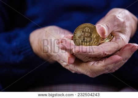 Senior Woman Holding Bitcoins And Demonstrating One Of Them. Selective Focus.