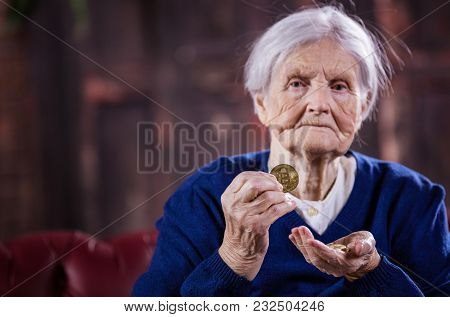 Senior Woman With Couple Of Bitcoins, Demonstrating One Of Them, Hands In Focus
