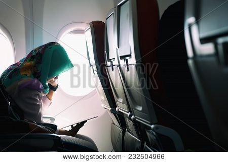 Female Lonely Muslim Traveling On Plane While Reading On Seats During A Sunset, Lowlight Ambience Mo