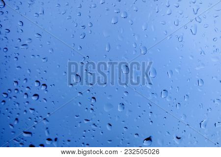 Glass with drops of rain water close up with blue color