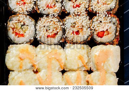 Various Kinds Of Hot Fried Sushi Rolls Served On Table.