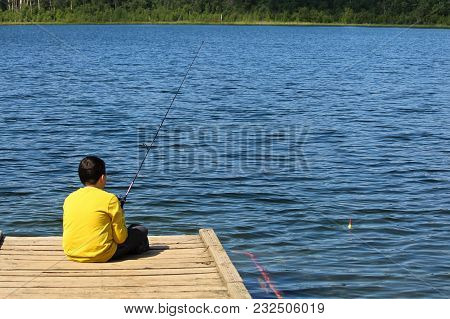 A Young Boy Sitting On A Dock And Fishing.