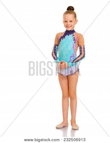 A Nice Little Girl Gymnast, In A Beautiful Gymnastic Swimsuit For Competitions. In Full Growth. The