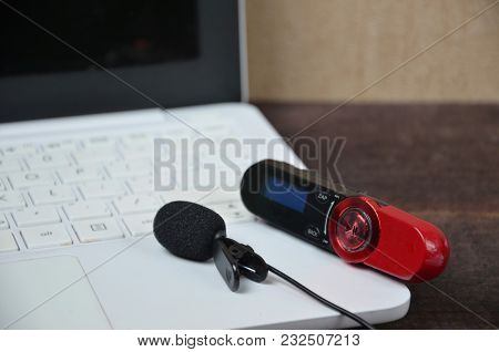 Laptop Dictaphone And Microphone On A Wooden Table. Journalist, Online Training, Remote Work.