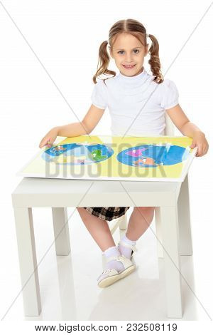 A Little Girl In Montessori Kindergarten Sits At A Table And Studies Montessori Stuff. The Concept O