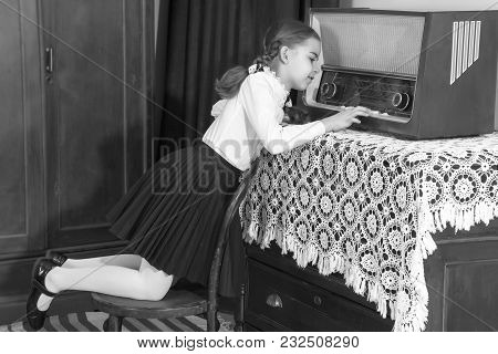 A Beautiful Little Schoolgirl Girl In A White Blouse And Black Long Skirt, With Neatly Braided Pigta