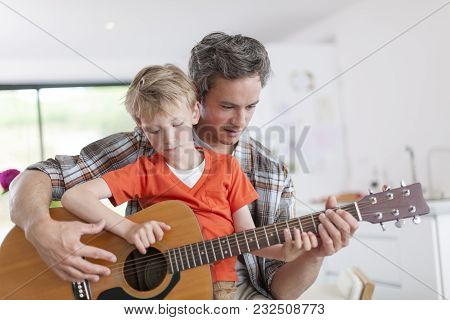 Father Learning His Boy To Play Guitar.
