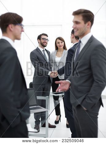Portrait of businessman talking  while  colleagues shaking hands