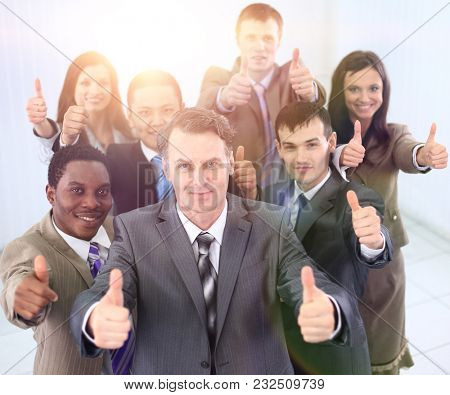 happy business team holding thumbs up