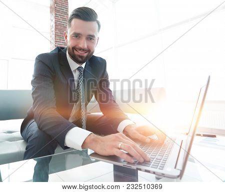 Successful man working on laptop in modern office