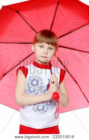 A Nice Little Blonde Girl With A Short Bangs. In A Red Skirt And A White T-shirt With A Pattern. The