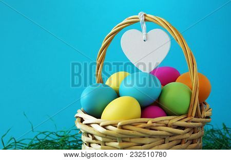 Colorful Easter Eggs Basket On Green Grass Greeting Card With Copy Space And A Blank White Wooden He