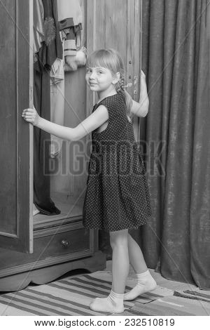 A Nice Little Girl Looks In The Old Wardrobe Wardrobe. The Concept Of Fashion, Retro Style, Things O