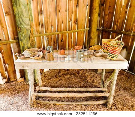 Interior Of A Native American Dwelling With A Carved Wooden Table Set With Utilitarian Objects Such