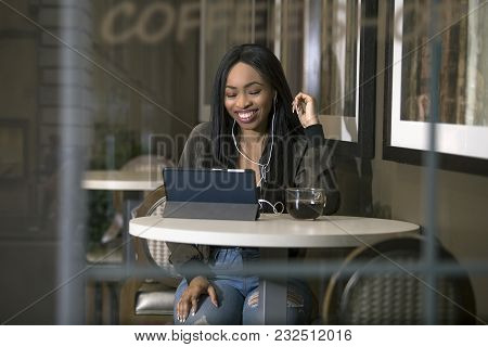 Window View Of A Black Female Wearing Headphones And Watching Videos On A Tablet In A Coffeeshop Str