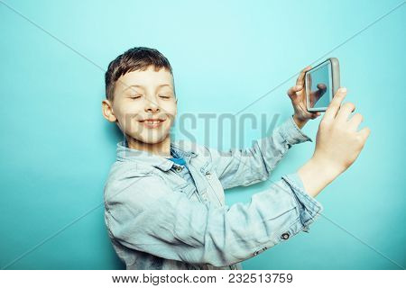Little Cute Boy Posing Emotional On Blue Background With Smartphone, Lifestyle People Concept Close