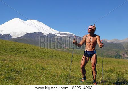 Athletic Naked Man, A Tourist, Stands On The Alpine Meadow And Joyfully Stares Into The Distance.the