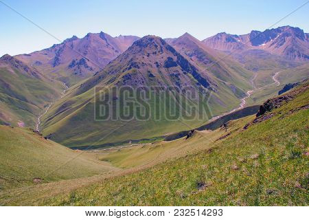 Wild Mountain Valley With A River. View From A Height. Green Grassy Slopes, High Blue Sky. Peaceful