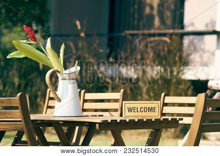 Welcome Sign Put On A Wooden Table With A Chair In The Middle Of The Lawn. Decorated With Vintage Fl