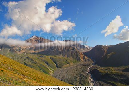 Wild Mountain Valley With A River. View From A Height. Green Grassy Slopes, High Blue Sky With Cloud