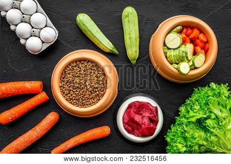 Dry Pet Food With Natural Ingredients. Raw Meat, Vegetables Zucchini And Carrot Near Eggs On Black B