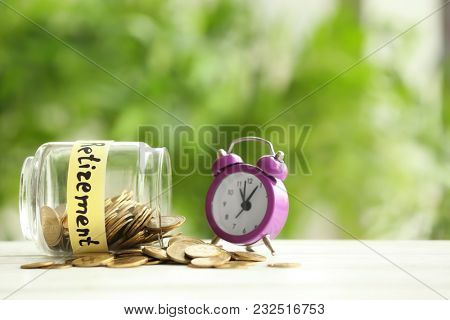 Glass jar with coins and alarm clock on blurred background. Time for pension planning