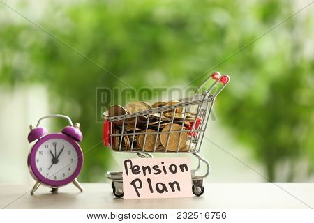 Shopping cart with coins and alarm clock on table against blurred background. Time for pension planning