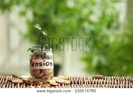 Plant growing from glass jar with coins on wicker surface against blurred background. Pension planning concept