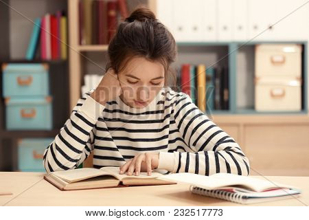 Cute teenager girl doing homework in library