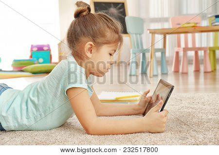 Cute little girl using tablet PC while doing homework indoors