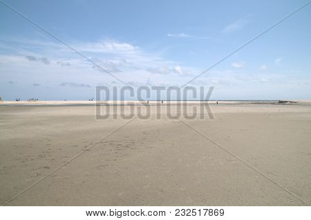 Vast Open Sand Dune With People Walking Along The Shore Of The Atlantic Ocean In The Background Unde