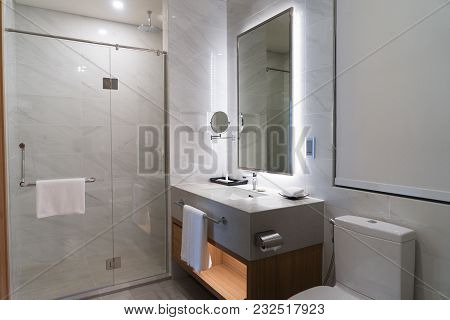 Illuminated Contemporary Bathroom With Clean Towels Hanging On Handles Of Shower Stall And Cupboard