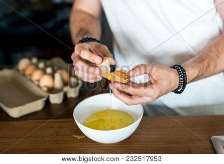 Closeup of man separating egg yolk