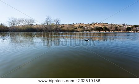 Beautiful Lake View Shot With Wild Ducks Swims At The Lake. Desert Mountains With Houses View By The