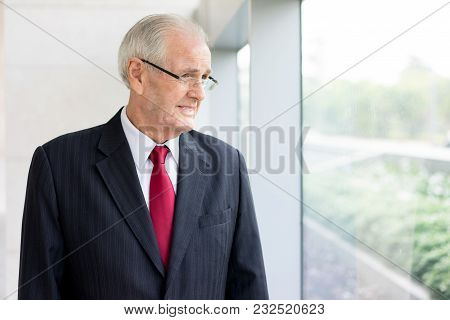 Closeup Portrait Of Pensive Senior Man In Suit Looking Out Panoramic Window Of Office Building. Seni