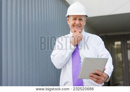 Concerned Man In Formalwear And Helmet Using Tablet At Site And Touching Chin. Construction Controll