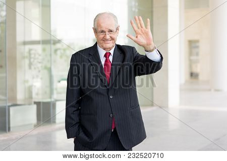 Friendly Senior Man In Suit Waving With Hand In Greeting Outdoors. Financial Consultant Having Break