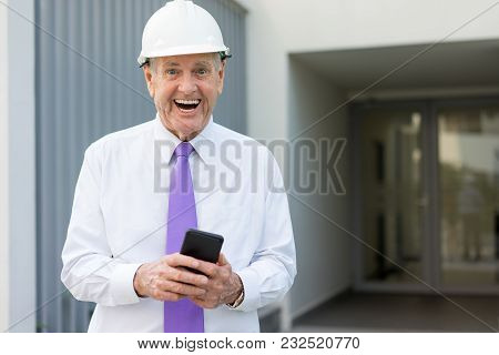 Happy Senior Man In Formalwear And Helmet Using Phone At Construction Site. Excited Building Owner G