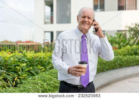 Joyful Senior Man In Formalwear Speaking On Mobile Phone And Drinking Takeaway Coffee Outdoors. Busi