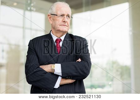 Portrait Of Serious Senior Man In Suit With Arms Crossed Outdoors With Glass Exterior In Background.