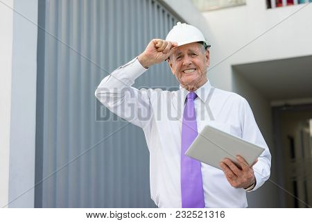 Portrait Of Smiling Senior Man In Formalwear And Helmet Holding Tablet. Construction Company Executi