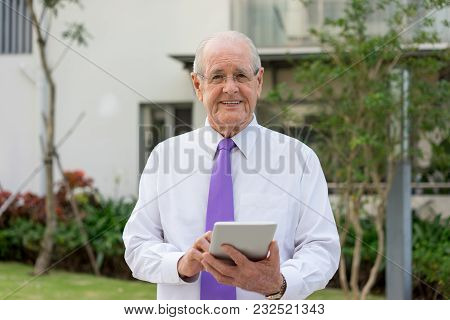 Smiling Senior Man In Formalwear And Glasses Using Tablet Outdoors. Businessman Checking Email In Re