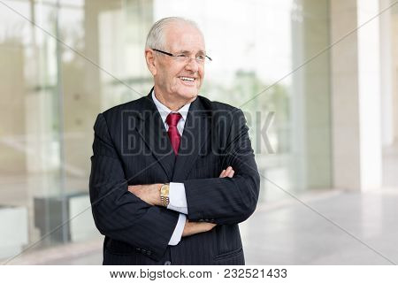 Portrait Of Smiling Senior Man In Suit With Arms Crossed Outdoors. Experienced Consultant Smiling To