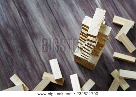 Wooden Building Blocks Tower On Dark Wood Background With Copy Space. Wood Blocks Stack Game Backgro